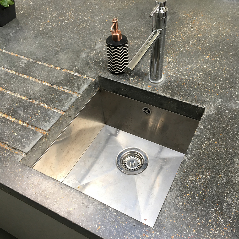 Conscious Forms - hither green giant l shaped peninsular concrete island worktop heavily ground surface finish with sloping drainage grooves sink tap cutouts detail