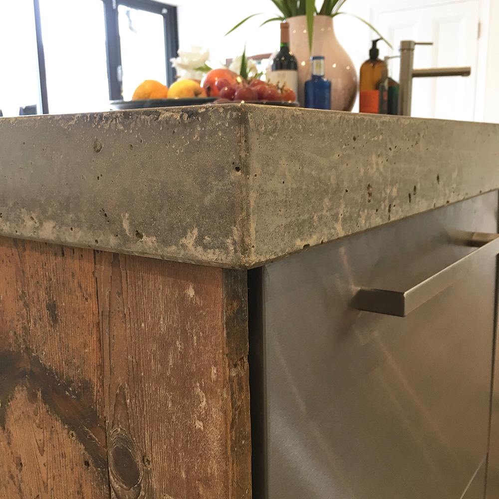 Conscious Forms - peckham london 80mm thick concrete island worktop with reclaimed timber end panel and stainless steel doors detail