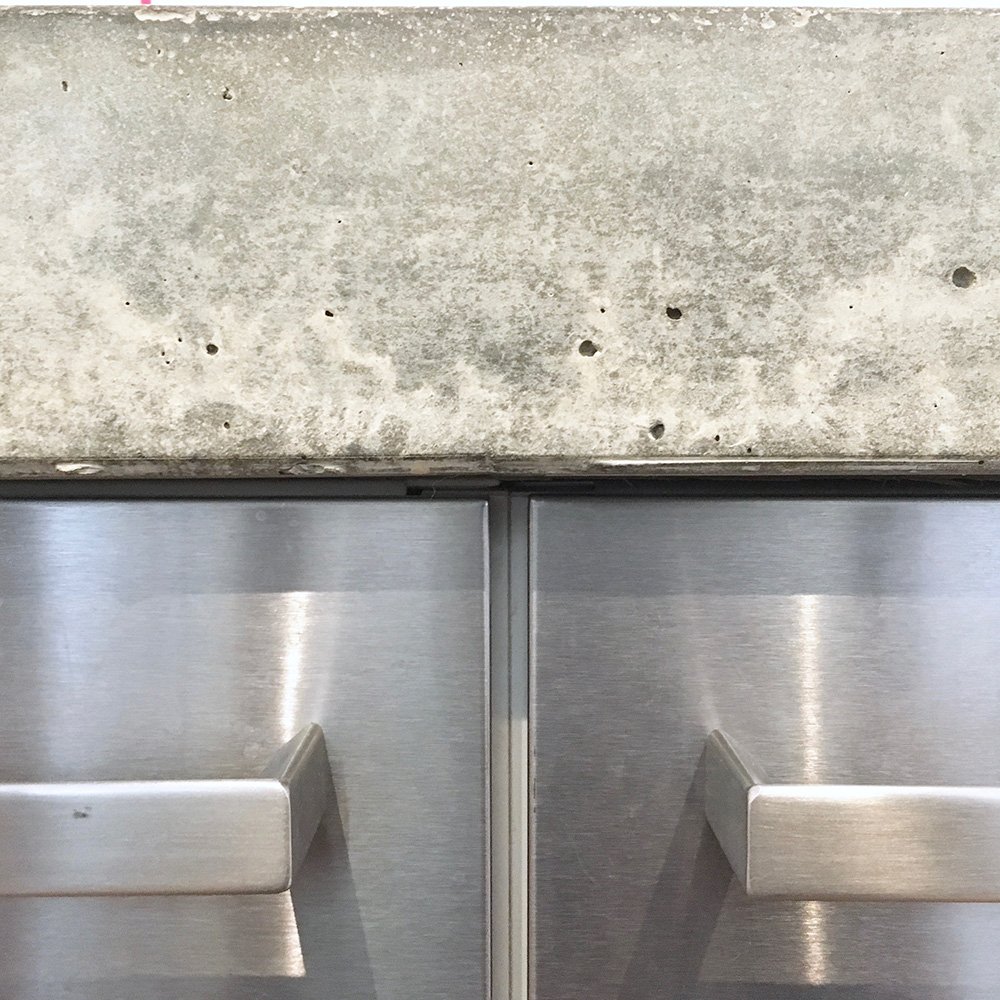 Conscious Forms - peckham london 80mm thick concrete island worktop with stainless steel cabinet doors detail